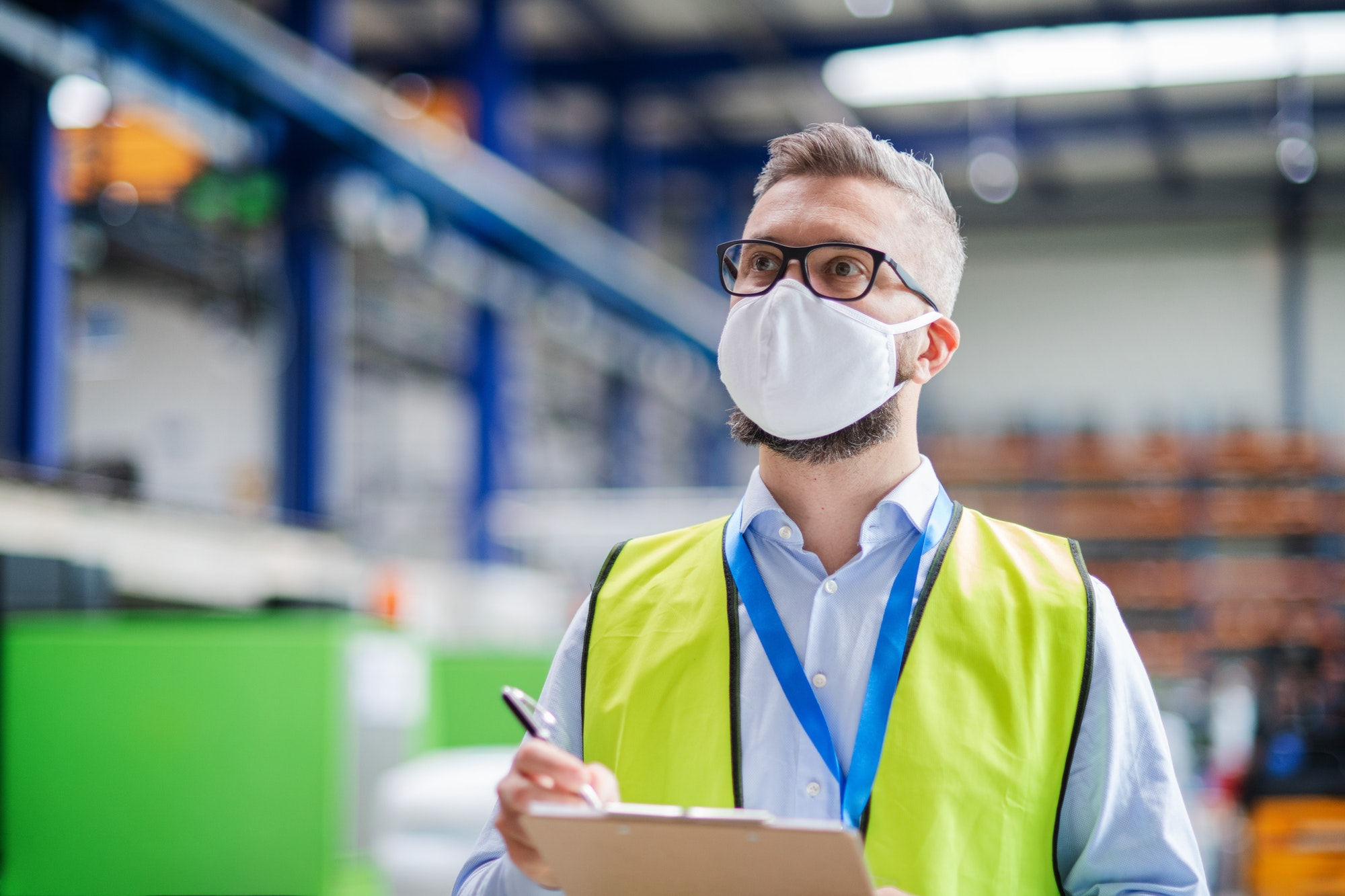 Technician or engineer with protective mask working in industrial factory, walking